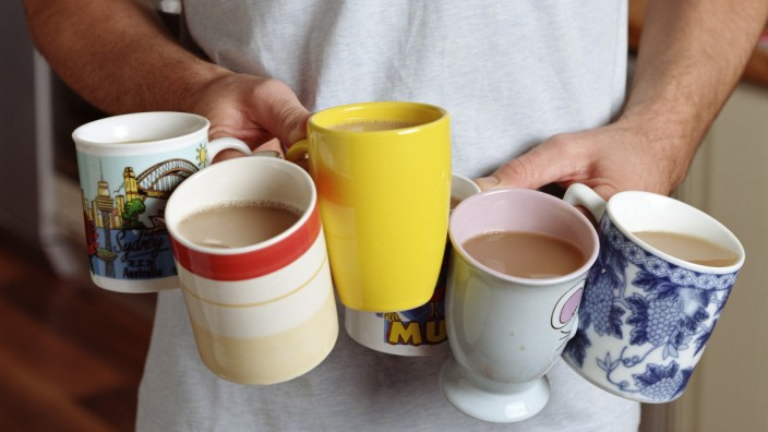 Man holding six cups of tea, mid section