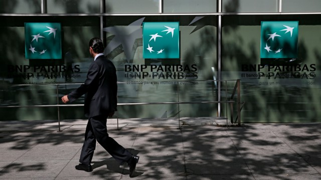 A man walks past a BNP Paribas bank office in Madrid