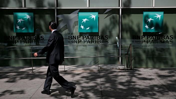 A man walks past a BNP Paribas bank office in Madrid