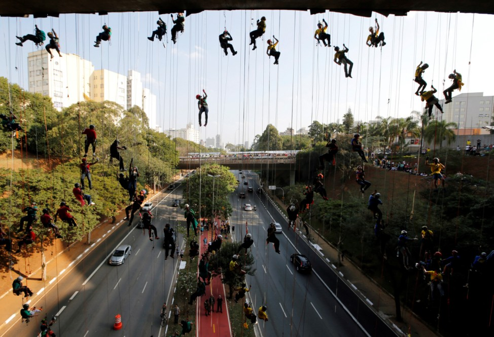 People rappel from a bridge to form the Olympic rings in Sao Paulo