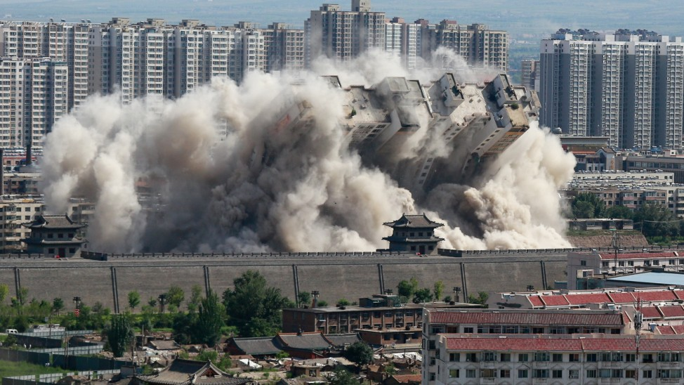 A building crumbles during a controlled demolition conducted to better protect the nearby ancient area of the city in Datong
