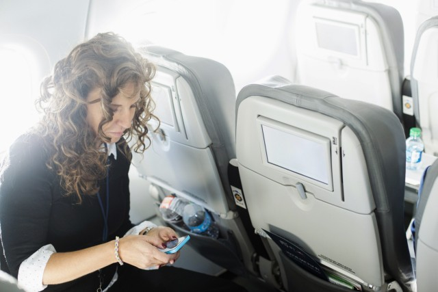 A woman uses her mobile phone to test a new high speed inflight Internet service named Fli-Fi while on a special JetBlue media flight out of John F. Kennedy International Airport in New York