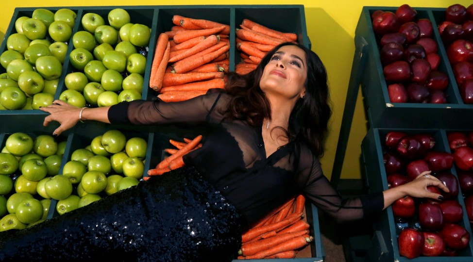 Cast member Hayek lays on fruit and vegetables as she poses at the premiere for the movie 'Sausage Party' in Los Angeles
