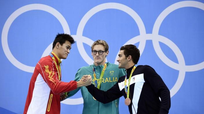 Olympia: Höflich abgeklatscht, doch Australiens Mack Horton (Mitte) äußerte deutliche Kritik am einst wegen Doping gesperrten Sun Yang (li.)