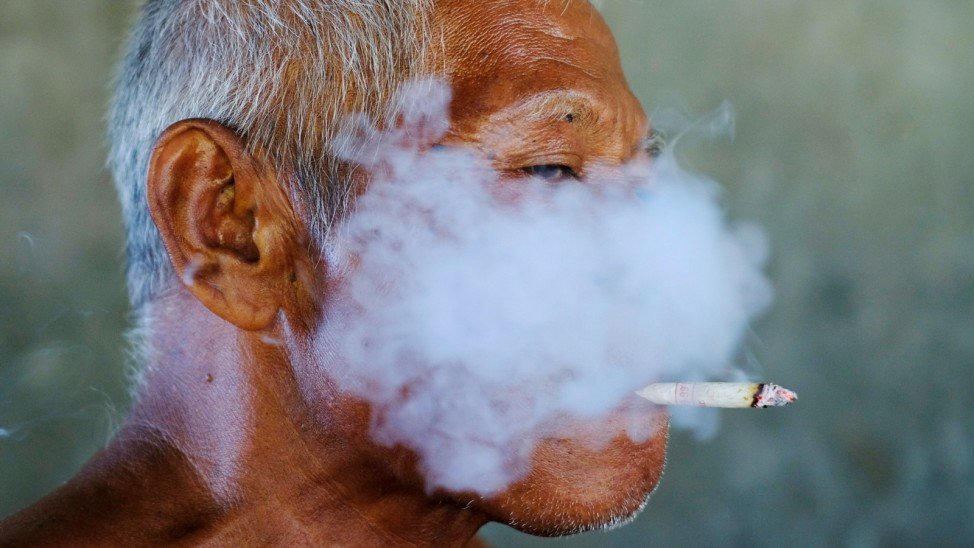 A worker smokes a cigarette during a break at a fabric factory in Solo