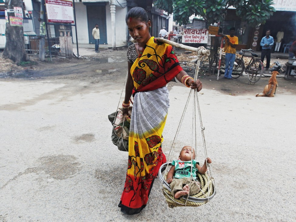 A woman carries her child in a basket as she walks on a road in Allahabad