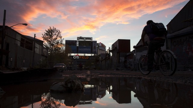 Man rides a bicycle through a street in the Willets Point area of Queens in New York.