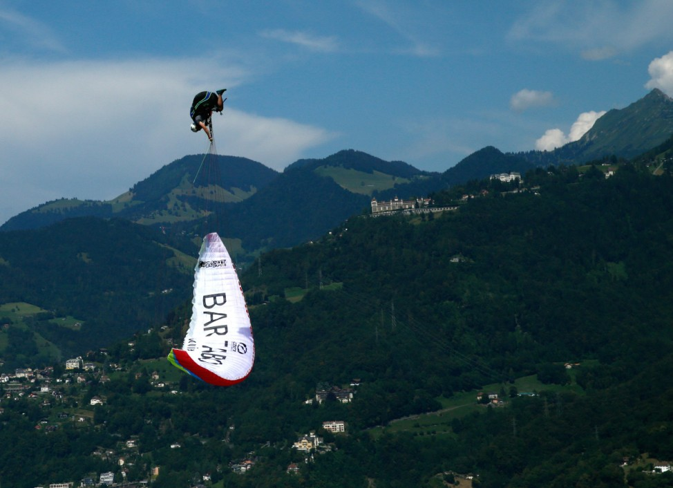 Montavon, pilot of the Swiss Acro League, performs an infinity tumbling maneuver while paragliding above Lake Leman during a training session before the Acroshow competition in Villeneuve, Switzerland