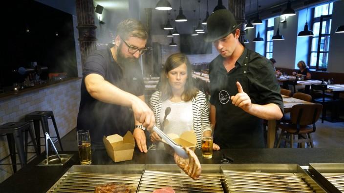 Grill & Grace: Der Grillmeister erklärt, die Griller grillen und trinken dazu ein Bier, wie es sich gehört. Nur dass die Gäste hinterher nicht aufräumen müssen.