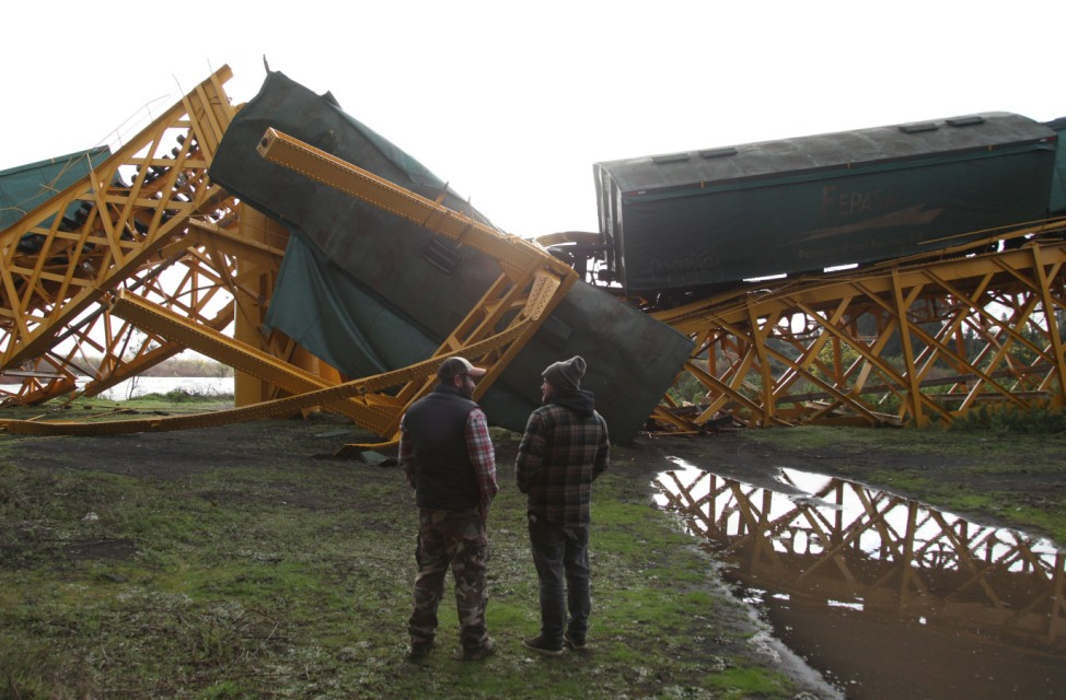 Wagons of a freight train are seen next to the Tolten river after a bridge collapsed in Pitrufquen village, in the Araucania region, south of Chile