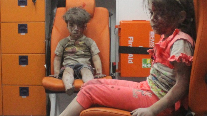 Five-year-old Omran Daqneesh, with bloodied face, sits with his sister inside an ambulance after they were rescued following an airstrike in the rebel-held al-Qaterji neighbourhood of Aleppo