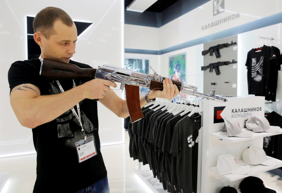 A salesperson demonstrates a model AK-47 assault rifle at the newly opened Gunmaker Kalashnikov souvenir store in Moscow's Sheremetyevo airport