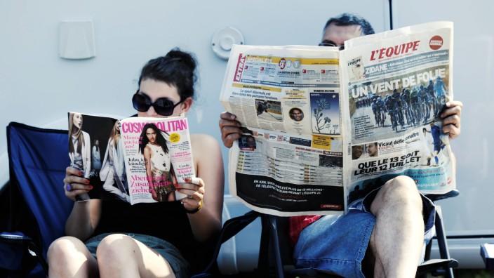 Tour de France 2013 Zuschauer warten auf die Fahrer und lesen Zeitung