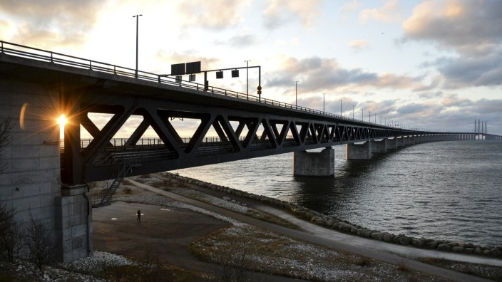 The sun sets over the Oresund Bridge between Sweden and Denmark, in Malmo