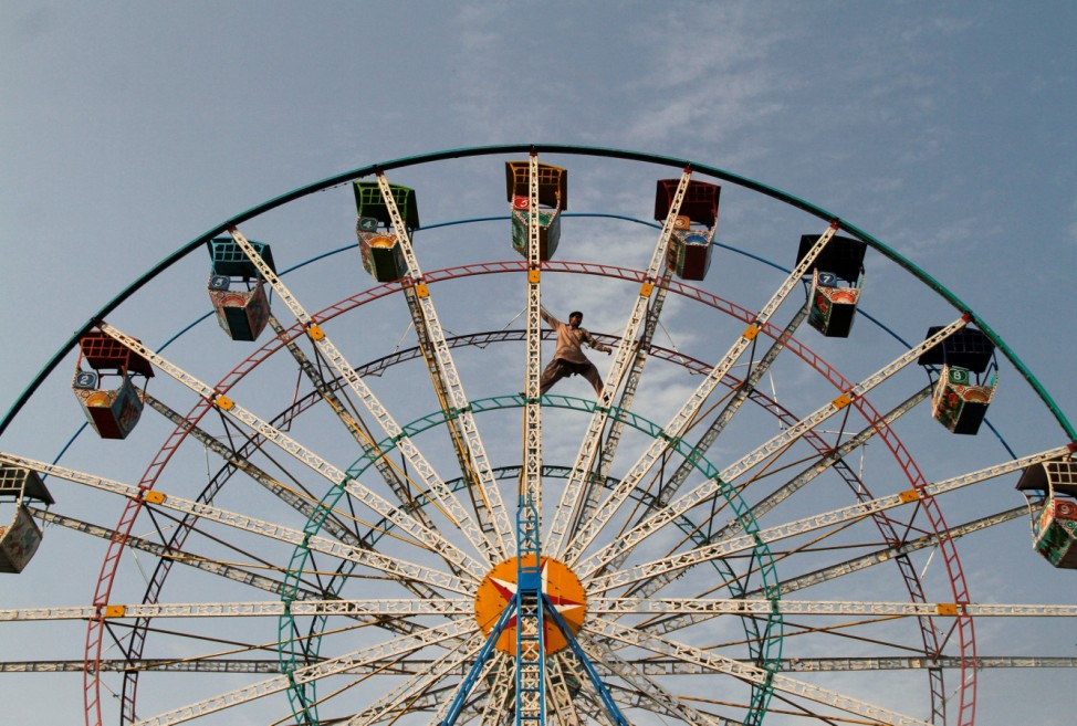 A man balances himself on a Ferris wheel as he inspects it at a public park in Sardaryab