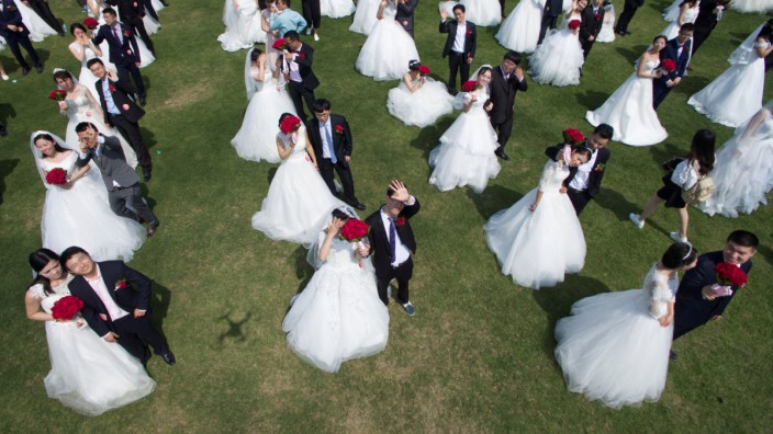 Newlywed couples attend a mass wedding ceremony in Hangzhou