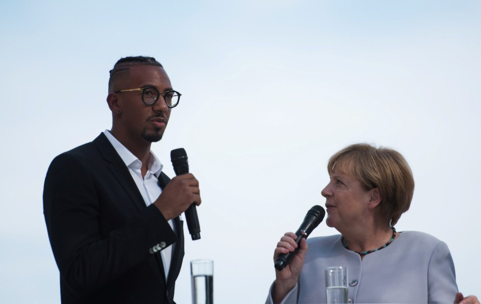 German Chancellor Angela Merkel talks with Jerome Boateng during the open day at the Federal Chancellery in Berlin