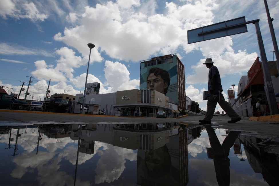 Man crosses a street while looking at a mural of late iconic Mexican singer Juan Gabriel, in Ciudad Juarez