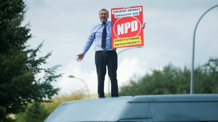 Udo Pastoers stands on a car during a visit by German Chancellor Angela Merkel in Greifswald