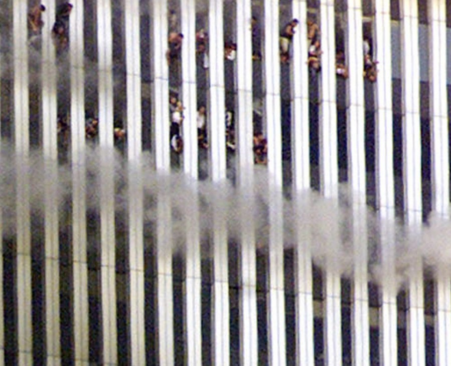 PEOPLE LOOK OUT OF WINDOWS AS WORLD TRADE CENTER BURNS