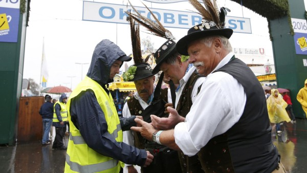 People walk past a security fence on the opening day of the 183rd Oktoberfest in Munich