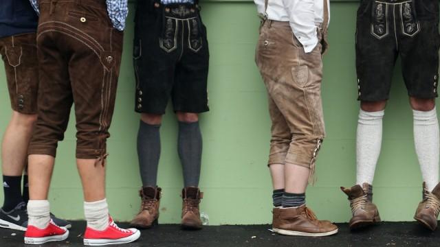 Oktoberfest-Outfits: Männer in Lederhosen stehen vor einer Wand