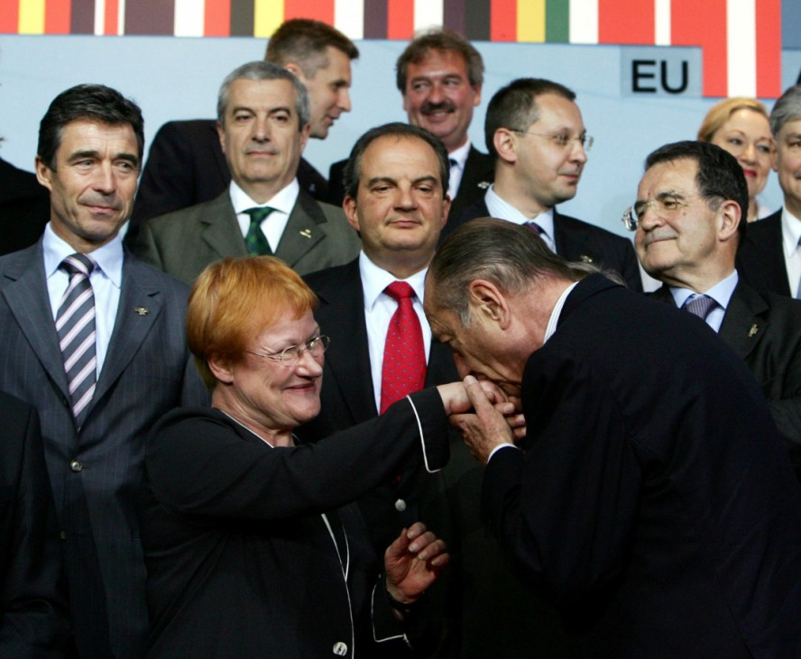 France's President Jacques Chirac kisses the hand of Finland's President Tarja Halonen during the family photo session of a EU summit in Brussels