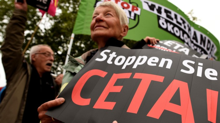 Consumer rights activists hold banners as they protest against CETA during Social Democrats meeting in Wolfsburg