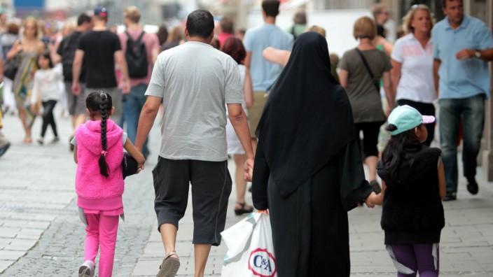 muslimische Familie mit verschleierter Frau gehen durch die Innenstadt Muenchen Bayern Deutschland