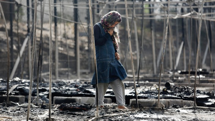 A migrant stands among the remains of a burned tent at the Moria migrant camp, after a fire that ripped through tents and destroyed containers during violence among residents, on the island of Lesbos
