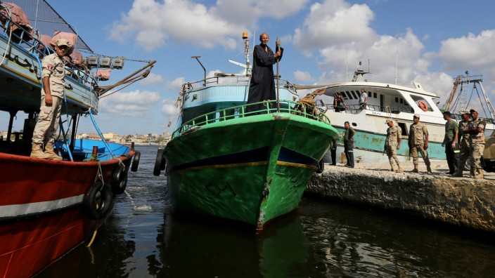 A relative of a missing person from a boat carrying migrants which capsized off Egypt's coast, stands on a fishing boat in front of an army camp during a search for victims, in Al-Beheira