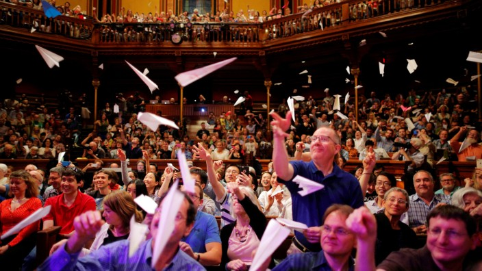 Audience members throw paper airplanes at the stage during the 26th First Annual Ig Nobel Prize ceremony at Harvard University in Cambridge