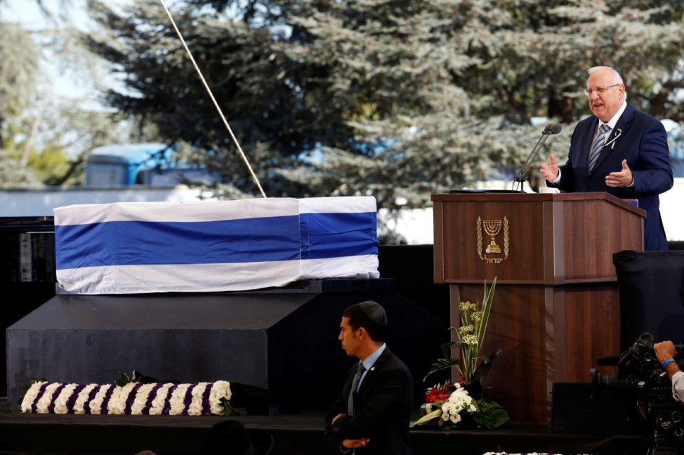 Israeli President Rivlin eulogises former Israeli President Shimon Peres, as his flag-draped coffin is seen nearby, during the funeral ceremony at Mount Herzl cemetery in Jerusalem