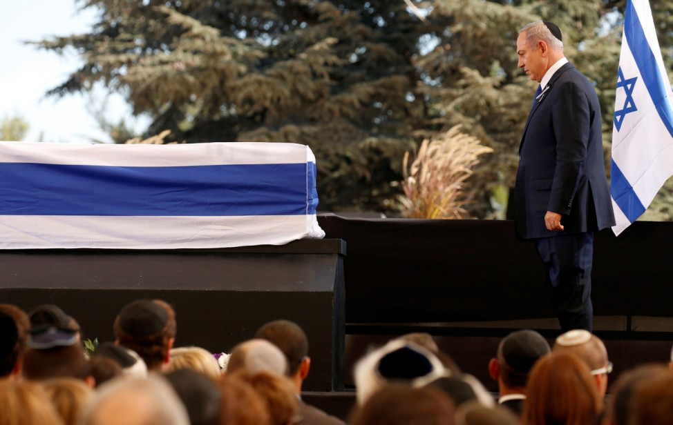 Israeli PM Netanyahu stands in front of flag-draped coffin of former Israeli President Shimon Peres, during the funeral ceremony at Mount Herzl cemetery in Jerusalem
