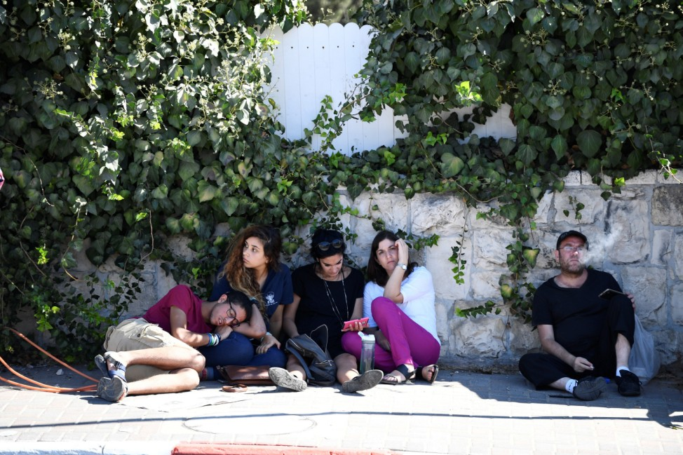 Israelis sit outside near Mount Herzl cemetery as funeral ceremony for former Israeli President Shimon Peres takes place in Jerusalem