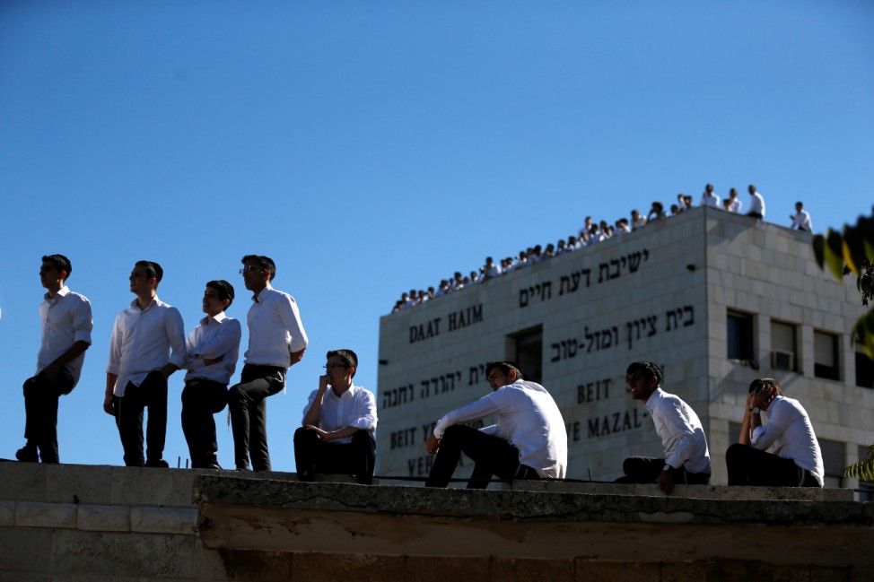 Ultra-Orthodox Jewish youths stand atop a wall near Mount Herzl cemetery before the start of the funeral ceremony for former Israeli President Shimon Peres in Jerusalem