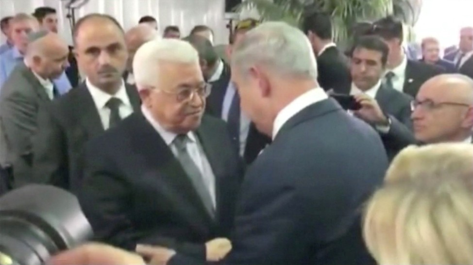Still image taken from video shows Palestinian President Abbas shaking hands with Israel's PM Netanyahu at funeral of former Israeli President Peres in Jerusalem