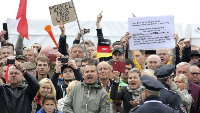 Police watches protestors holding a placard 'Merkel must go' during celebrations marking the German Unification Day in Dresden