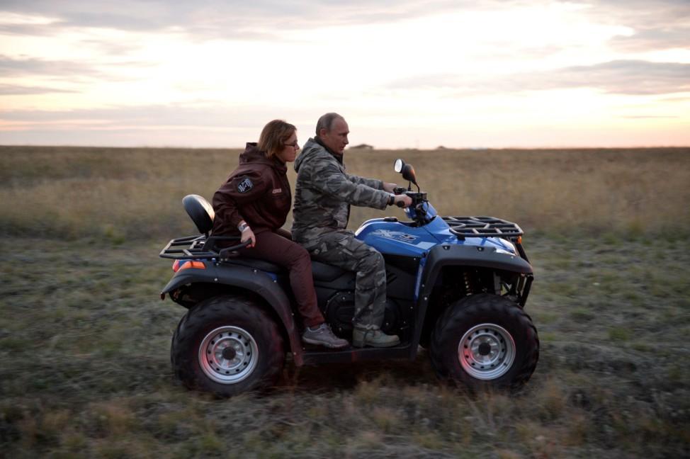 Russian President Putin drives a quad bike as he visits a reserve for Przewalski's horses outside Orenburg