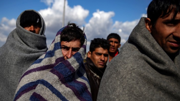 Refugees and migrants try to warm themselves as they take a break at a petrol station before abandoning their trek to the Hungarian border, in the town of Indjija