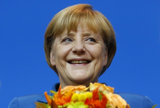 Merkel smiles as she receives flowers after first exit polls in Berlin