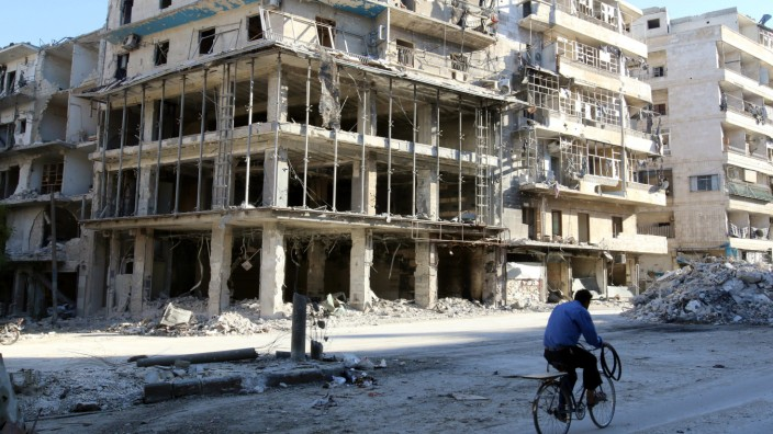 A man rides a bicycle near damaged buildings in the rebel held besieged al-Sukkari neighbourhood of Aleppo