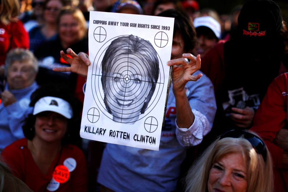 A supporter of Republican U.S. presidential nominee Donald Trump holds a shooting target with image of Hillary Clinton at a campaign rally in Virginia Beach