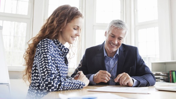 Businessman and woman at desk discussing plans model released Symbolfoto property released PUBLICATI