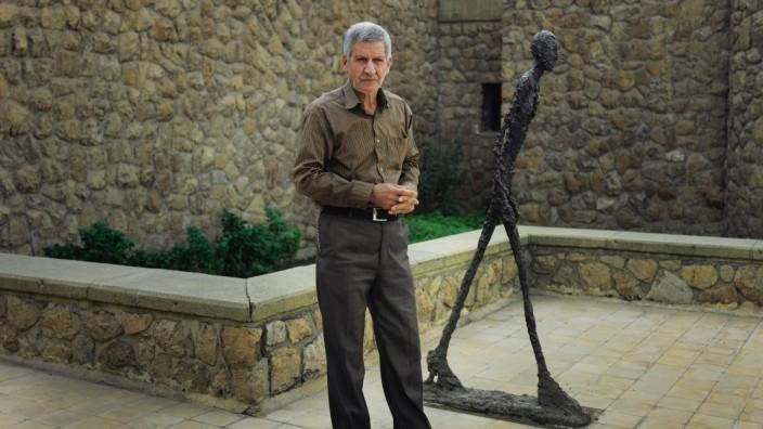 Westliche Kunst in Teheran: Firouz Shahbazi neben einer seiner Lieblingsskulpturen, Walking Man I von Alberto Giacometti.