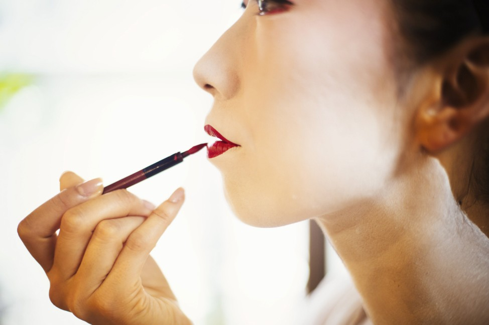 A modern woman creating the traditional geisha vivid red lips by painting on lipstick with a fine br