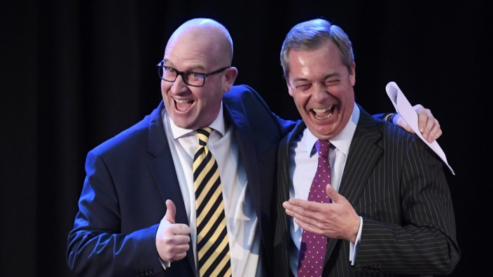 United Kingdom Independence Party interim leader Nigel Farage embraces newly elected leader Paul Nuttall, in London