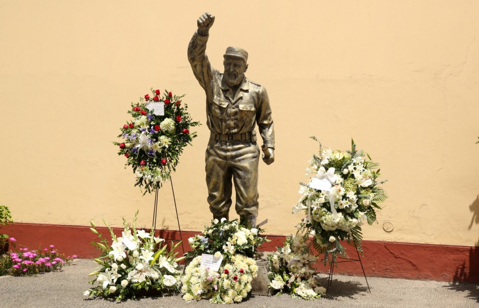 Flowers are seen next to a statue of Cuban revolutionary leader Fidel Castro following the announcement of his death inside the Cuban embassy in Lima,