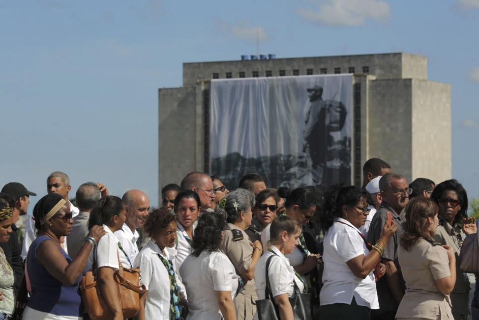 A large portrait of Cuba's late President Fidel Castro hangs from a building while people wait in line to pay tribute to Castro in Havana