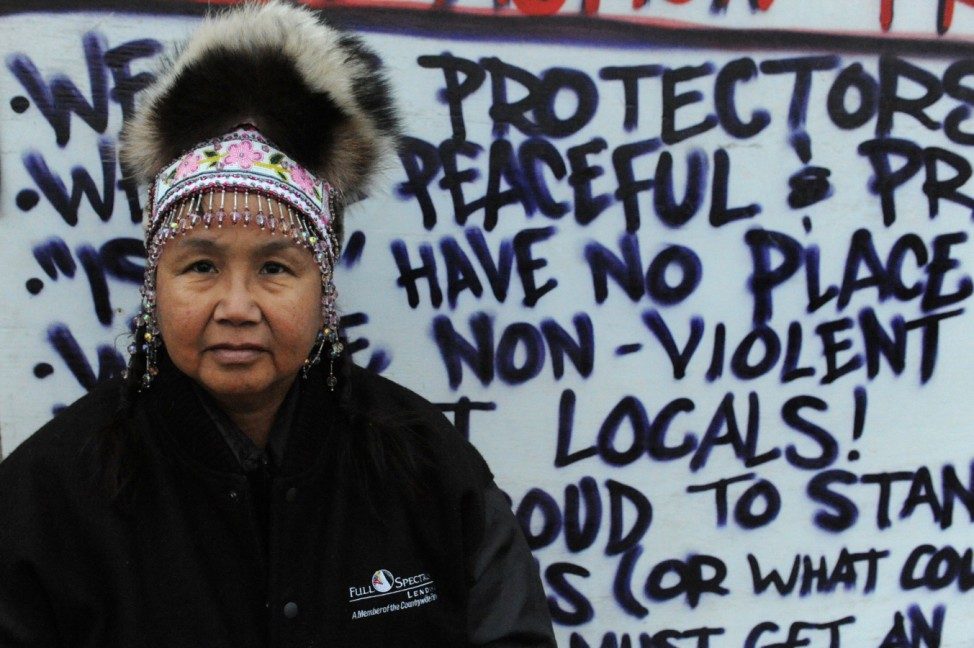 Bedushia Nicholi poses for a photograph in front of the information board in an encampment during a protest against plans to pass the Dakota Access pipeline near the Standing Rock Indian Reservation